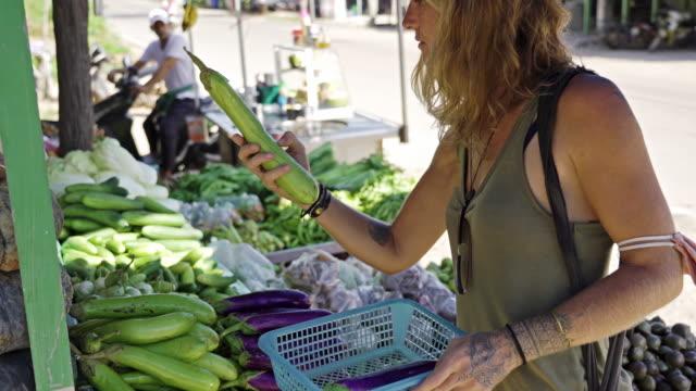 vídeos de stock, filmes e b-roll de mulher tatuada vegetal orgânico compras de rua fresca mercado tailândia tailândia - plano americano