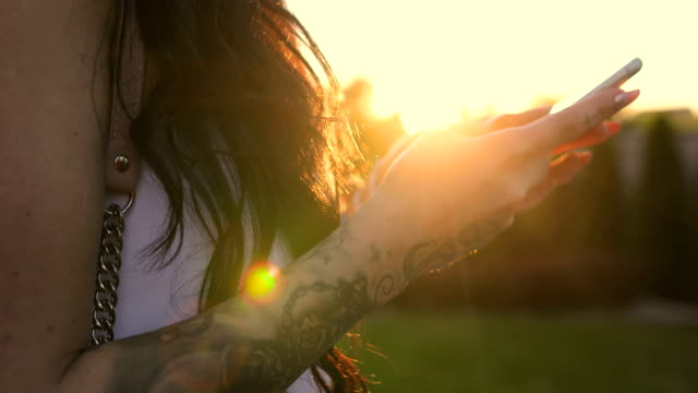 tattooed woman using smartphone at sunset - back lit stock videos & royalty-free footage