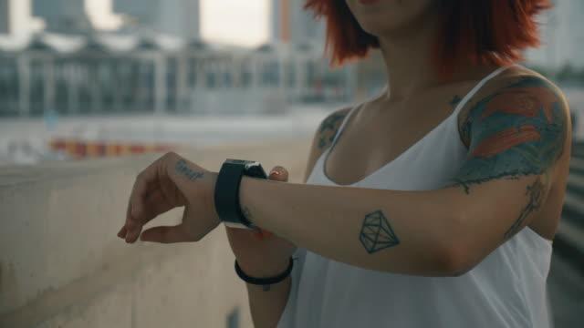 Tattooed woman wearing a smartwatch in a urban scene