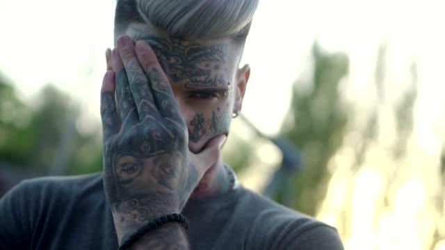 vídeos de stock e filmes b-roll de tattooed young man outdoors - tatuagem