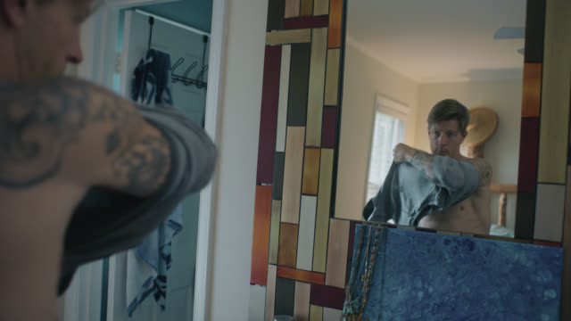 tattooed young man with one arm puts on shirt in front of mirror - t shirt stock-videos und b-roll-filmmaterial