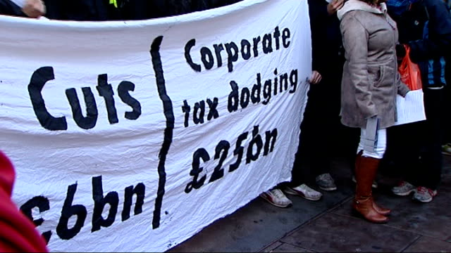 tax office criticised for being too cosy with big businesses r17121101 ext tax avoidance protesters with banner and chanting sot - avoidance stock videos & royalty-free footage