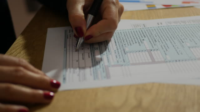 vídeos de stock e filmes b-roll de taxation in usa and tax form 1040 - businesswoman filling out the document - relatório