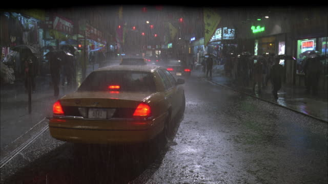 WS Taxi cab pulls away from curb and drives down a rainy city street