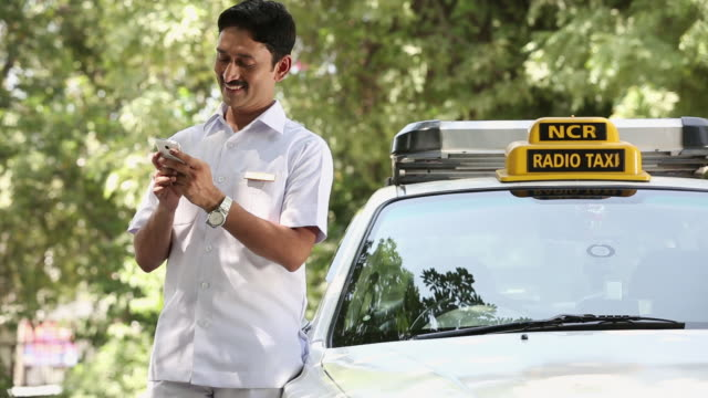 taxi driver dialing a mobile phone, delhi, india  - taxi driver stock videos and b-roll footage