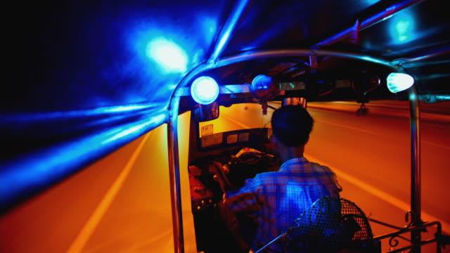 WS T/L POV Taxi driver driving tuk-tuk at night in the streets of Bangkok / Bangkok, Thailand