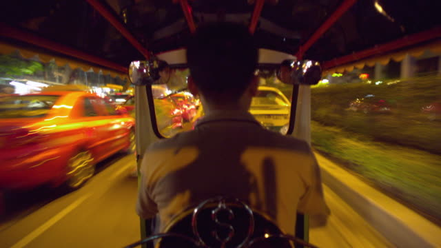 t/l ms pov taxi driver getting in stationary tuk tuk then driving through city streets at night, bangkok, ayuthaya, thailand - see other clips from this shoot 1448 stock videos and b-roll footage