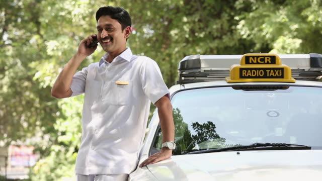 vídeos y material grabado en eventos de stock de taxi driver talking on a mobile phone, delhi, india  - taxista