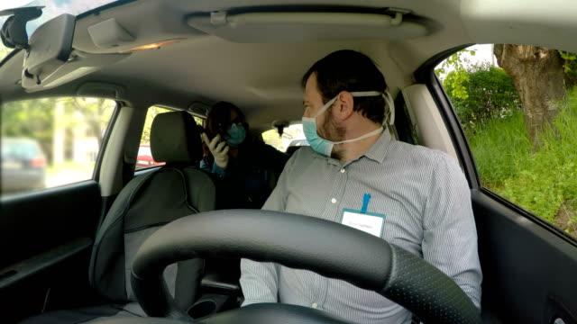 vídeos y material grabado en eventos de stock de taxista hablando con una pasajera. concepto de virus corona - pasajero