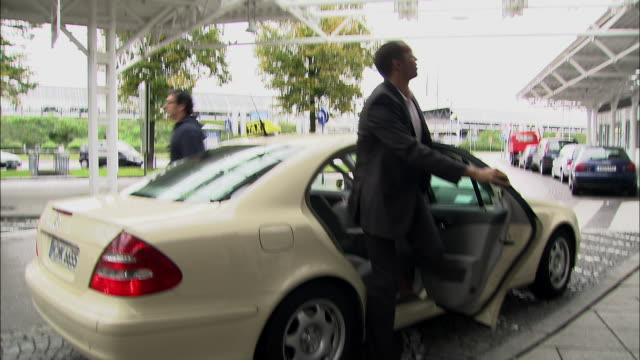 ms ws zi taxi driver unloading suitcase from trunk of car for businessman who enters airport / munich, germany - rinnsteinkante stock-videos und b-roll-filmmaterial
