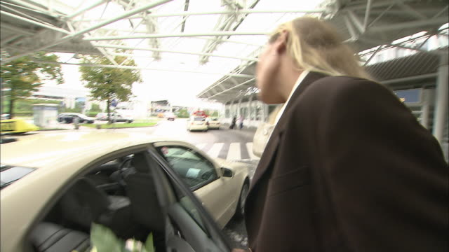 stockvideo's en b-roll-footage met ms tu ts taxi driver unloading suitcases from trunk for businessman and businesswoman who enter airport / munich, germany - münchen vliegveld