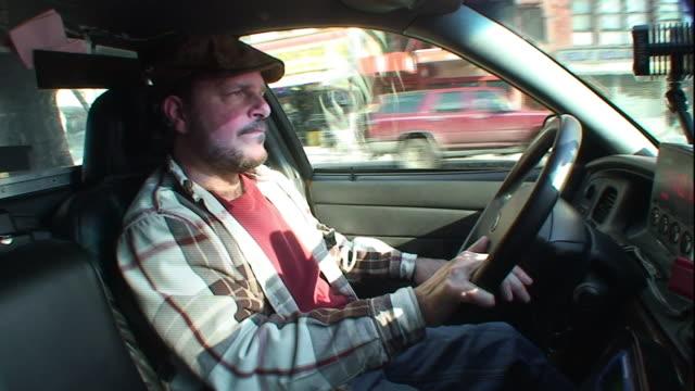 vídeos y material grabado en eventos de stock de a taxi driver wearing a hat drives through a street in new york city. - taxista