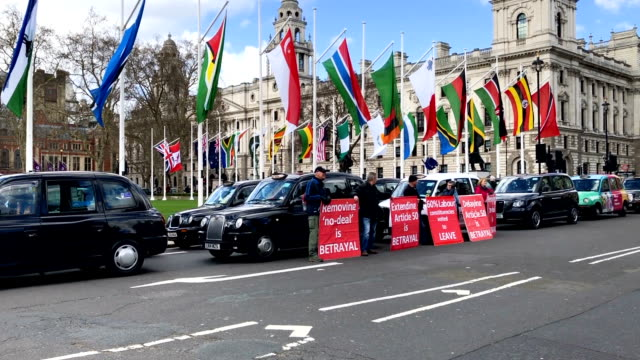 Taxi drivers hold Brexit themed placards as they stage a Black Cab demo outside the Houses of Parliament in Westminster on March 11 2019 in London...