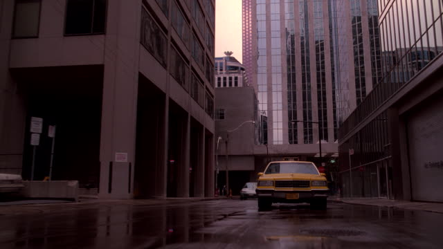 a taxi drives on a wet downtown street. - wet wet wet stock videos & royalty-free footage
