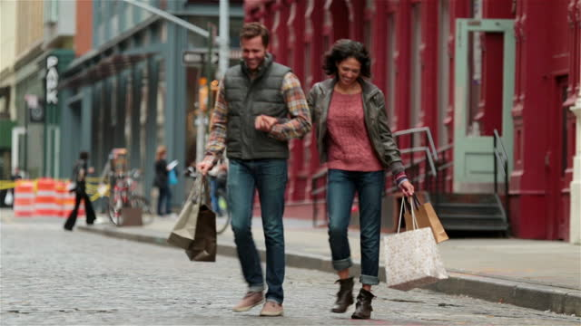 Taxi drives past, happy New York couple with shopping bags hurriedly cross Soho street hand-in-hand (dolly-shot)