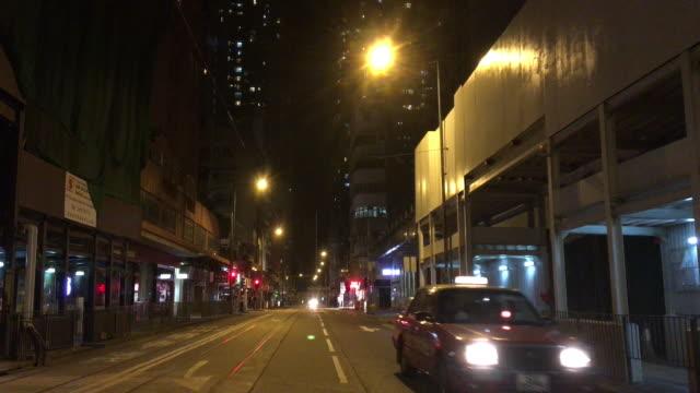 vidéos et rushes de taxi conduite vers la caméra, hong kong street night - ligne de tramway