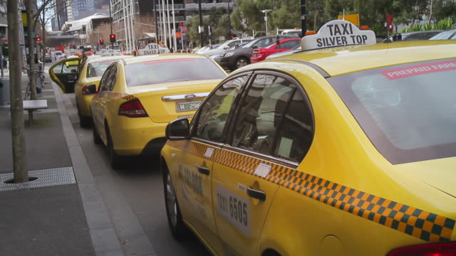 MS T/L Taxi moving in rank at road side / Melbourne, Victoria, Australia