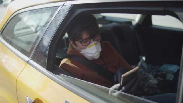 vidéos et rushes de passager de taxi utilisant des masques protecteurs avec le téléphone intelligent pendant la pollution atmosphérique ou l'épidémie de maladie - yellow taxi