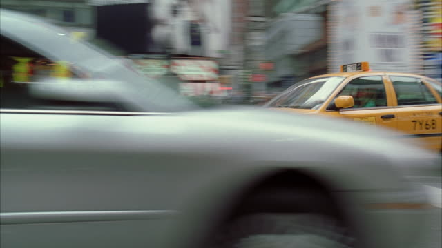 ms pan taxi pulling into car park at high speed amidst city traffic / new york city, new york state, usa - 横滑り点の映像素材/bロール