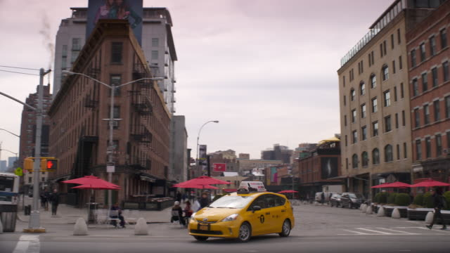 taxi turning onto 14th street in the meatpacking district in manhattan - taxi stock videos & royalty-free footage