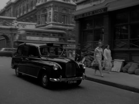 a taxi turns into derby gate road and approaches the new scotland yard building 1958 - ロンドン ホワイトホール点の映像素材/bロール