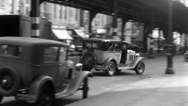 a 1937 taxicab weaves around the pillars of an el train bridge, nearly hitting a second car. - 1937 stock videos & royalty-free footage