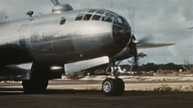 B29 taxiing on runway ground crewman directing bomber to parking spot and crewman exiting B29 hatch and dropping to the ground during WWII