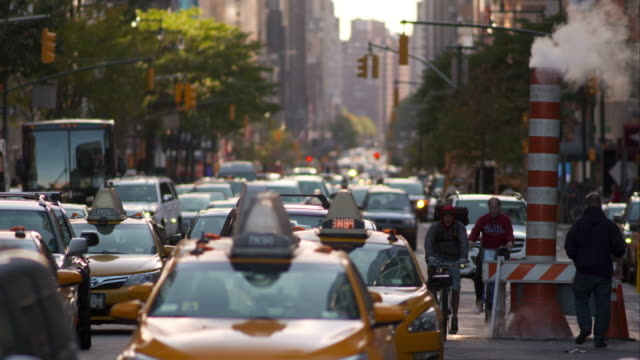Taxis and buses move along on busy New York City street. Steam rises from orange cone.
