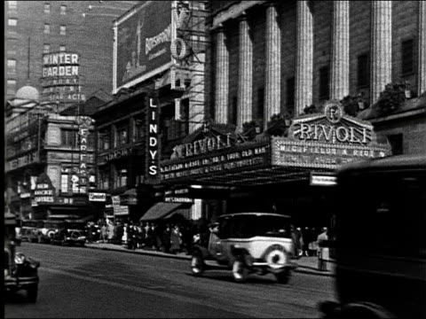 MS taxis and cars drive by Rivoli Theater and Lindys delicatessen at 49th and Broadway / Pan up Broadway showing Winter Garden sign / OS Times Square...