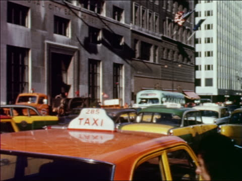 1960 REAR VIEW taxis in heavy traffic on city street / tilt down woman gets into taxi in foreground / NYC