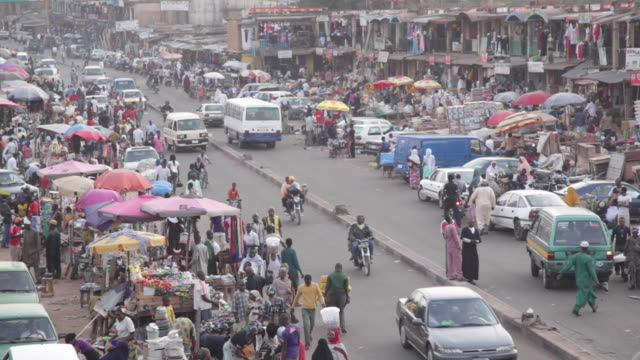 ha taxis moving through busy market street nigeria is home to nearly 200 million people which has earned it the name giant of africa it is an oil... - jos nigeria stock videos & royalty-free footage