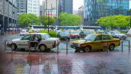 Taxi's stop to pick up passengers in front of a train station building in Fukuoka, Japan
