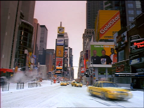 taxis + traffic going past camera in times square covered with snow / new york city - 1998 stock videos and b-roll footage