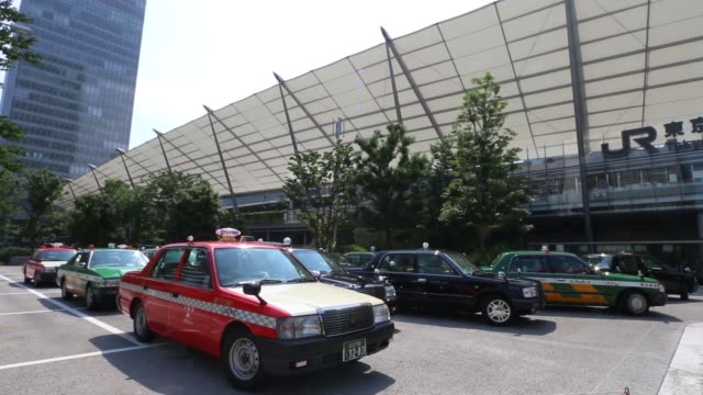 taxis wait in line at a taxi stand outside a train station in tokyo japan on monday july 11 a passenger enters a taxi at a taxi stand outside a train... - taxi stand stock videos and b-roll footage