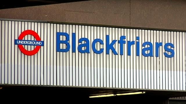 PJ Taylor interview SOT Sign above entrance for Blackfriars Underground Station Overland mainline trains along Commuters along platform at tube...