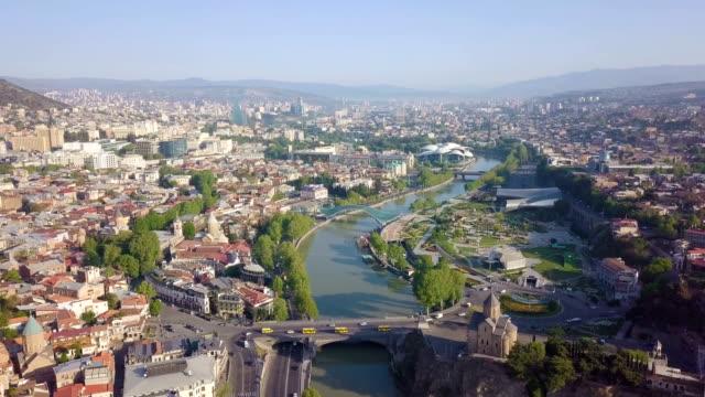 vídeos y material grabado en eventos de stock de tbilisi aerial cityscape with mtkwari river, bank of georgia and caucasus mountains in the background/ georgia, caucasus - georgia