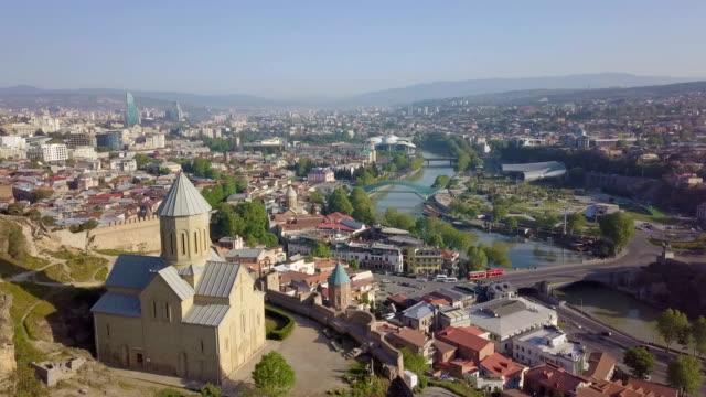 vídeos y material grabado en eventos de stock de tbilisi aerial cityscape with saint nicholas church, mtkwari river, narikala fortress and caucasus mountains in the background/ georgia, caucasus - georgia