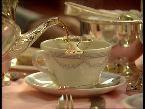 Tea being poured from silver teapot into china cup on saucer. Pan down a multi tiered tea tray with various cakes and sandwiches. Ritz Hotel.
