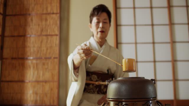 vídeos de stock, filmes e b-roll de anfitrião da cerimónia de chá que mede para fora água - washitsu