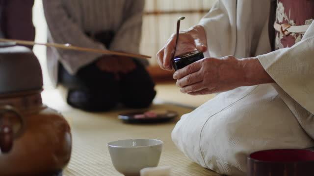 vídeos de stock, filmes e b-roll de chá da cerimónia do anfitrião que scooping o chá do caddy na bacia quando os convidados olham sobre - washitsu