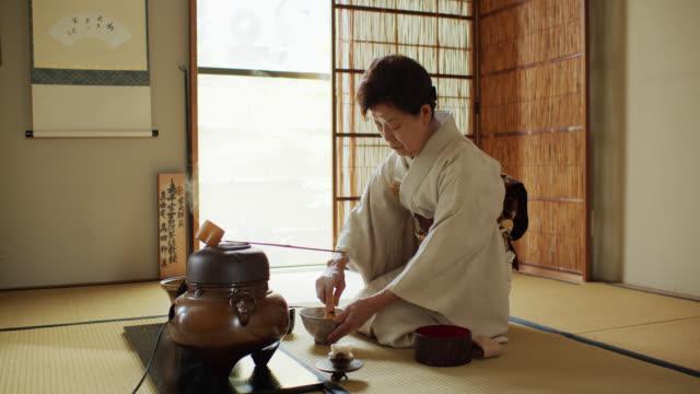 vídeos de stock, filmes e b-roll de anfitrião da cerimónia de chá usando whisk - washitsu