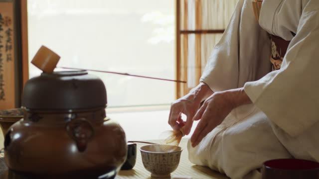 vídeos y material grabado en eventos de stock de el anfitrión de la ceremonia del té que bate y té remoteando en bowl - sado
