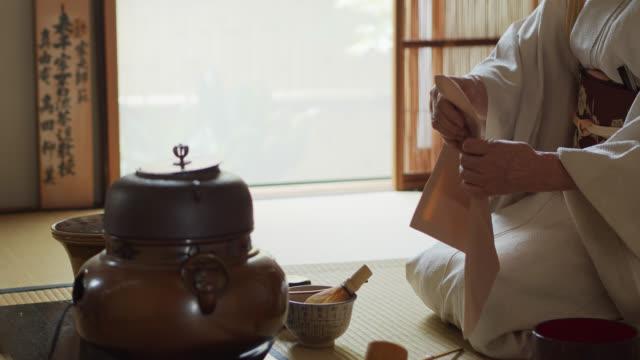 vídeos de stock, filmes e b-roll de anfitrião da cerimónia de chá que limpa o caddy com chakin - washitsu