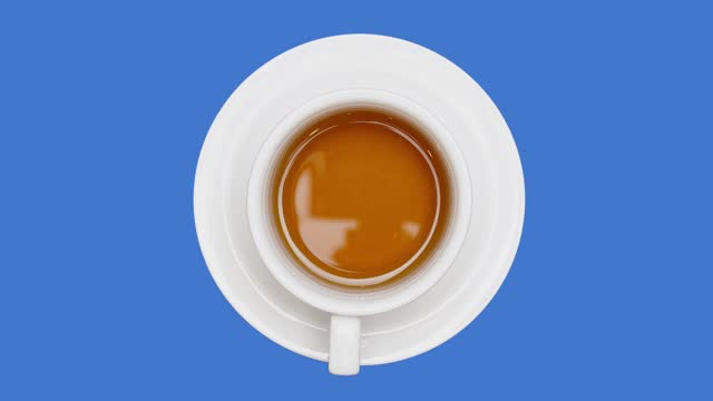 tea cup rotating on blue screen background top view. full to empty loop video - tea cup stock videos & royalty-free footage