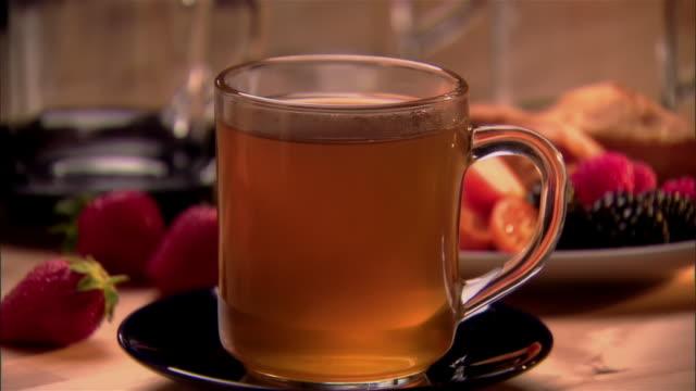 vídeos de stock, filmes e b-roll de selective focus, cu, zo, tea in glass cup and plate of fruits  - enfoque de objeto sobre a mesa