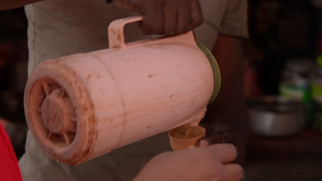 Tea is poured from a pink container into a terracotta cup at a street stall, Kolkata, India.