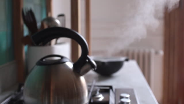 tea kettle emitting steam - bollente video stock e b–roll