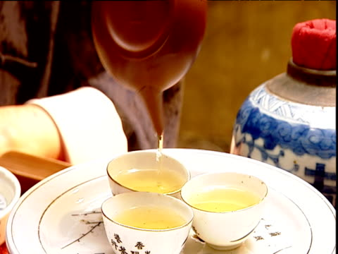Tea poured from small pot into three small cups at tea ceremony Hong Kong