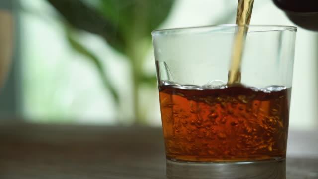 stockvideo's en b-roll-footage met thee die in glas op houten lijst giet - week