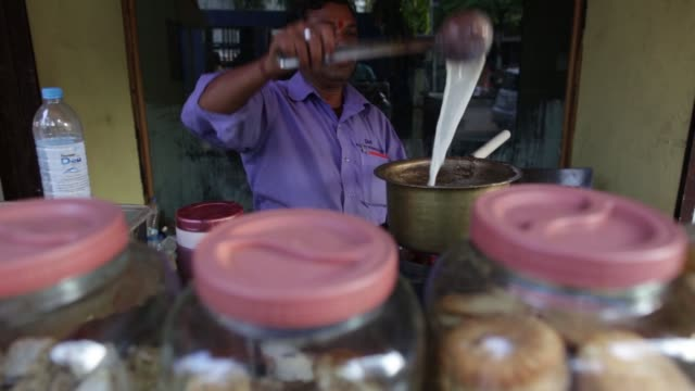 a tea vendor makes tea at a stall in navi mumbai maharashtra india on wednesday feb 24 cu tea vendor stirs a ladle in a saucepan of hot tea steam... - serving utensil stock videos and b-roll footage